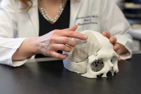 person pointing at a 3D printed skull