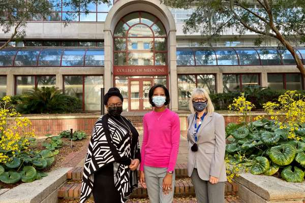 Three researchers stand together in front of the COM.