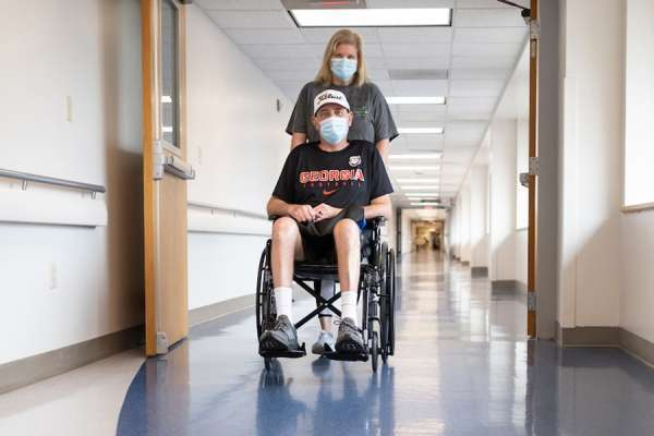 Mark Buchanan is wheeled down a hallway by his wife, Melissa, at the University of Florida Health Shands Hospital in January. Buchanan required a double-lung transplant to save his life after he contracted Covid-19.