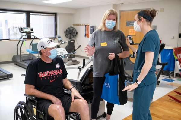 Mark, in a wheelchair, discusses his PT with his wife, Melissa, and their physical therapist, Katelyn Travaglini.