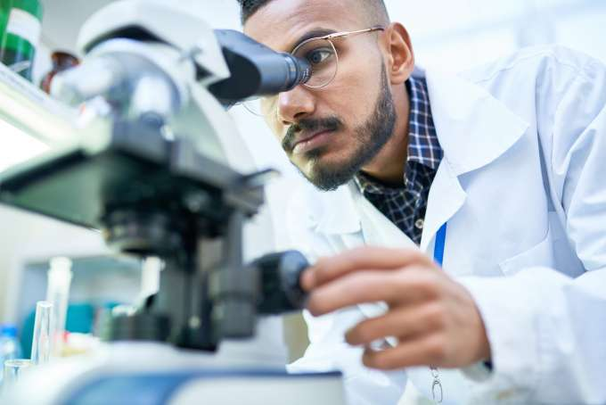 Portrait of young scientist looking in microscope while working on medical research in science laboratory, copy space