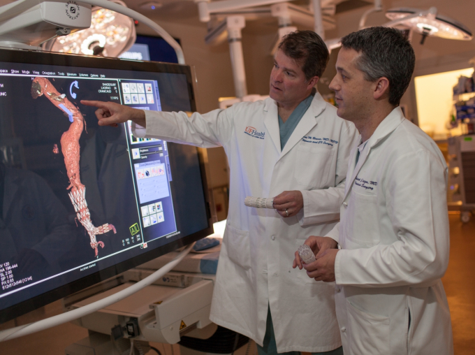 Doctors examining an image of a human body