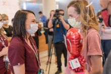 A nurse stands across from a double lung transplant patient. Both wear masks.
